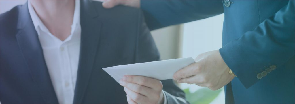 Image of two men passing an envelope between them
